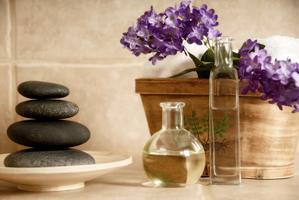 Steine auf einem Teller lila Blumenim Topf..davor zwei Massageöle